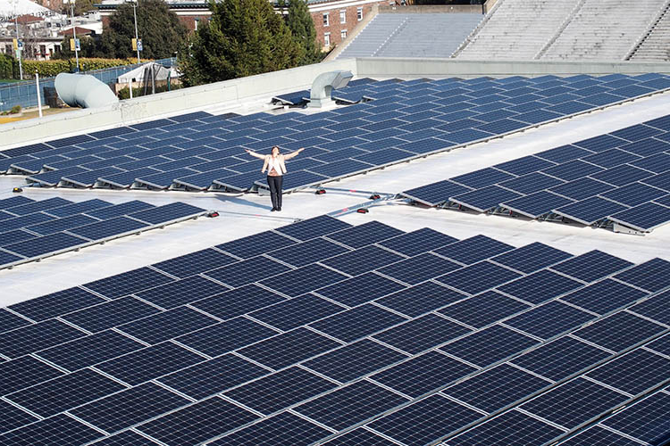 Kira Stoll, UC Berkeley's director of sustainability stands with solar panels on the top of the Recreational Sports Facility.