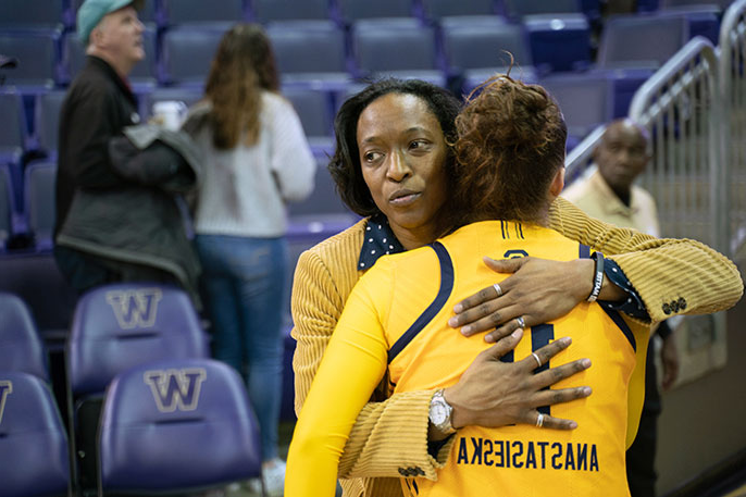 Charmin Smith consoles one of her players with a hug after a basketball game