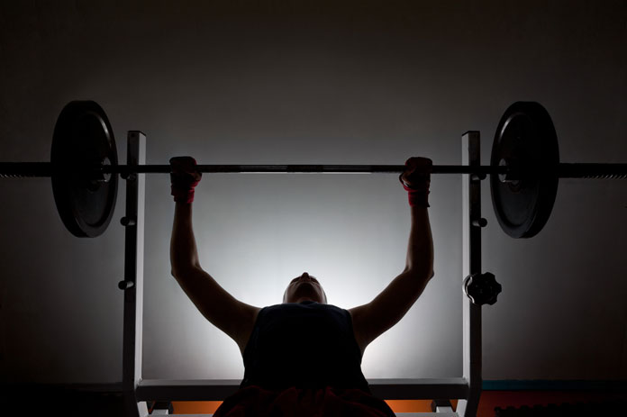 Man lifting weights in silhouette