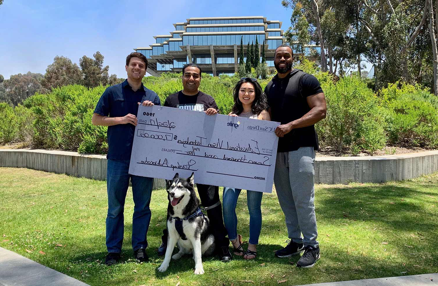 教育al Vision Technologies team members Lyn Scott, Shelly Bae and co-founders Monal Parmar and Jason Bunk hold first-place prize check after winning a pitch competition in June 2019.