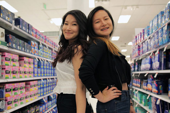 Lee sisters pose together in the feminine products aisle of a store
