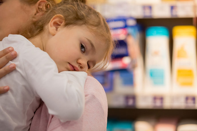 Child on parent's shoulder in front of personal care products