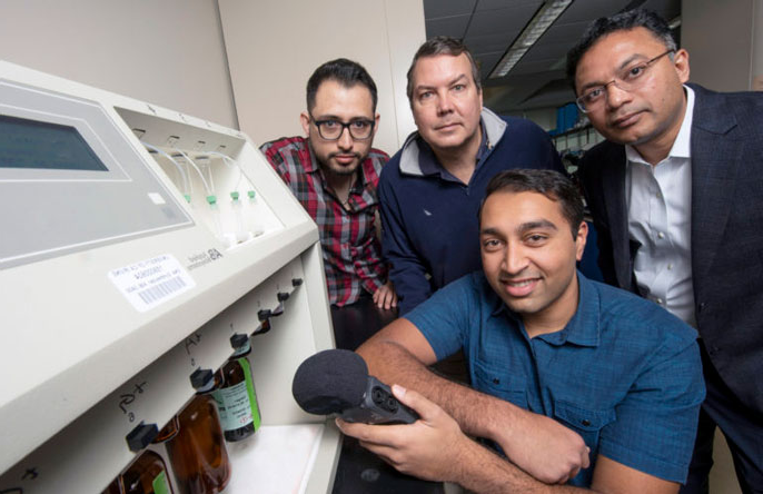 UC Irvine and UC Riverside researchers hold up a microphone to a DNA synthesizer