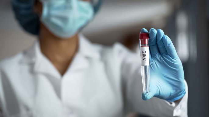 Woman holding a vial of blood in a lab